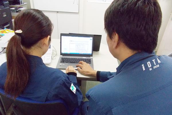 パソコン画面を見ながら部下に説明する男性社員