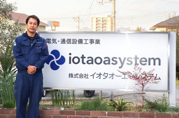イオタオーエーシステムの看板前に立つ採用担当者