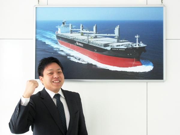 船の写真の前でガッツポーズで学生にエールを贈る採用担当者